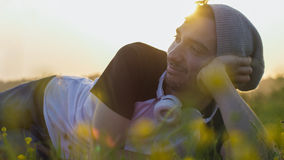 Happy young man smiling as he lays in a meadow at sunset Stock Image