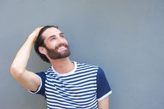 Happy young man smiling with hand in hair Royalty Free Stock Image