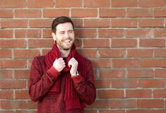 Happy young man smiling outdoors against brick wall background Royalty Free Stock Image