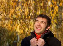 Happy young man smiling outdoors with winter jacket Stock Photo