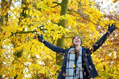 Happy young man smiling and throwing leaves with open arms. Portrait of a happy young man smiling and throwing leaves with open arms Royalty Free Stock Images