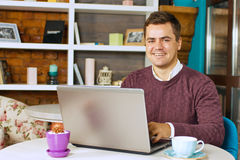 Happy young man smiling and works on his laptop Stock Photography