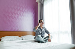 Happy young man speaking on cellphone in bedroom Stock Photo