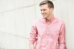 Happy young man standing against wall Stock Images