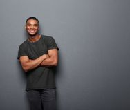 Happy young man standing with arms crossed Royalty Free Stock Photos