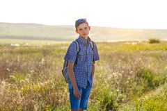 Happy young man standing with backpack outdoors on Sunny day royalty free stock photo