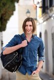 Happy young man standing on city street with bag Stock Photos