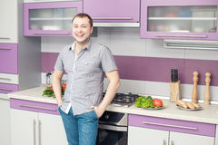 Happy young man standing in his modern kitchen Stock Photography