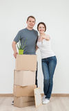 Happy young man standing near cardboard boxes,  his smiling wife Stock Photo
