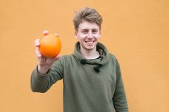 Happy young man standing on an orange background with an orange in his hands and smiling. Focus on the person.  royalty free stock image
