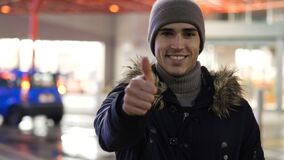 Happy young man standing outdoor at night in city. Handsome trendy happy young man standing outdoor at night in city setting doing thumb up sign in front of big stock video