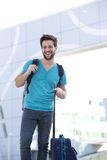 Happy young man standing outside with bags. Portrait of a happy young man standing outside with bags Royalty Free Stock Photos
