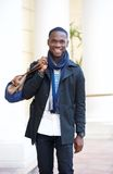 Happy young man standing outside hotel with bag Royalty Free Stock Images