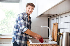 Happy young man standing and washing dishes on the kitchen. Happy young man in plaid shirt standing and washing dishes on the kitchen stock photography