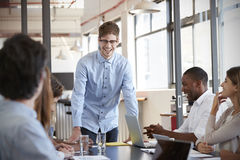 Happy young man stands addressing team at business meeting Stock Photos