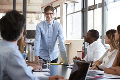 Happy young man stands addressing team at business meeting Royalty Free Stock Photo
