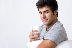 Happy young man with a steamy cup of coffee at home Royalty Free Stock Photo