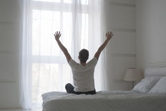 Happy young man stretching in bed after waking up, back view royalty free stock image