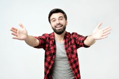 Happy young man stretching hands ahead, wanting to hug someone. Success positive emotions. Happy young hispanic man with beard stretching hands ahead, wanting to royalty free stock photo