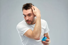 Happy young man styling his hair with wax or gel. Beauty, hairstyle, haircare and people concept - happy young man styling his hair with wax or gel over gray royalty free stock image