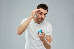 Happy young man styling his hair with wax or gel Royalty Free Stock Images
