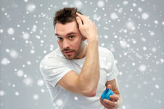 Happy young man styling his hair with wax or gel. Beauty, hairstyle, winter, christmas and people concept - happy young man styling his hair with wax or gel over Stock Photo