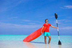 Happy young man with surfboard and paddle on the Royalty Free Stock Images