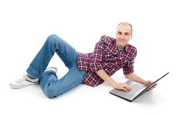 Happy young man surfing on laptop, lying down. Stock Photos