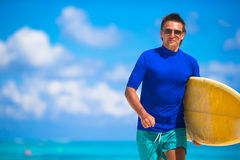 Happy young man surfing on the tropical coast Royalty Free Stock Photo