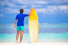 Happy young man surfing on the tropical coast. Strong young surf man runing at the beach with a surfboard Royalty Free Stock Photography
