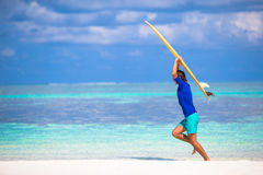 Happy young man surfing on the tropical coast. Strong young surf man runing at the beach with a surfboard Royalty Free Stock Photo
