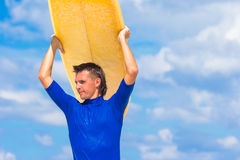 Happy young man surfing on the tropical coast. Strong young surf man runing at the beach with a surfboard Royalty Free Stock Photos
