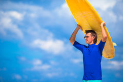 Happy young man surfing on the tropical coast. Strong young surf man runing at the beach with a surfboard Royalty Free Stock Images