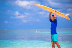 Happy young man surfing on the tropical coast. Strong young surf man runing at the beach with a surfboard Stock Images