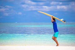Happy young man surfing on the tropical coast. Strong young surf man runing at the beach with a surfboard Stock Photo
