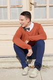 Happy young man in sweater sitting on steps in front of house royalty free stock photo