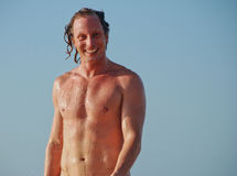 Happy young man after a swim on the beach Stock Photography
