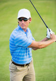 Happy young man swinging golf club Stock Photo
