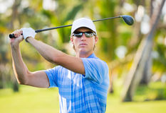 Happy young man swinging golf club Royalty Free Stock Photography