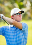 Happy young man swinging golf club Stock Images