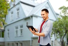 Happy young man with tablet computer over house stock photos
