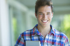Happy young man with tablet stock photography