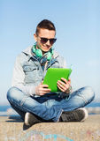 Happy young man with tablet pc and headphones Royalty Free Stock Photography