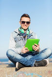 Happy young man with tablet pc and headphones Stock Photo