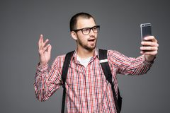 Happy young man taking self portrait photography through phone over gray background. Happy young man taking self portrait photography through smart phone over royalty free stock photography