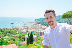 Happy young man taking selfie background the old coastal town of old italian city in Liguria Stock Images