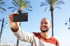 Happy young man taking a selfie with cell phone Stock Photos