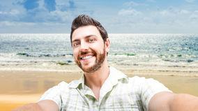 Happy young man taking a selfie photo on the beach Royalty Free Stock Photo