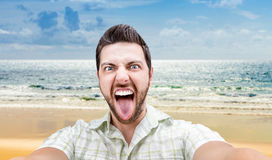 Happy young man taking a selfie photo on the beach Stock Photography