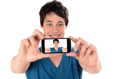 Happy young man taking a selfie photo with his smart phone. Stock Images